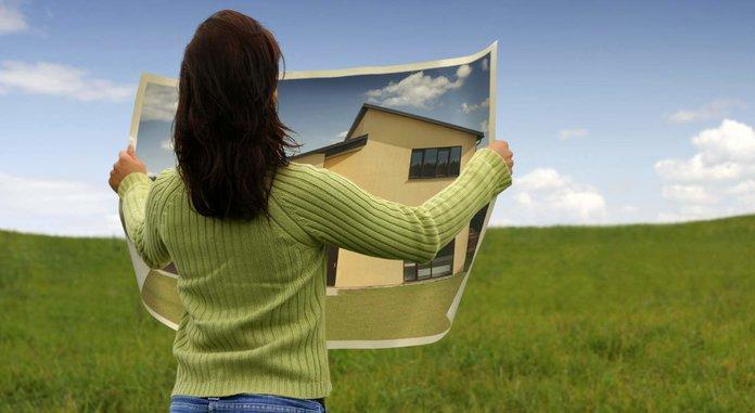 Женщина в поле с картиной дома