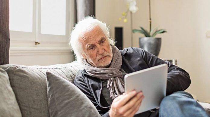 Старик читает на планшете