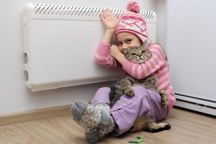 Девочка возле батареи с котом и в шапке