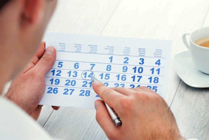 Мужчина делает пометки в календаре