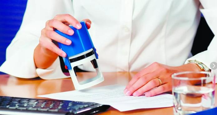 Сотрудница ставит печать на документе