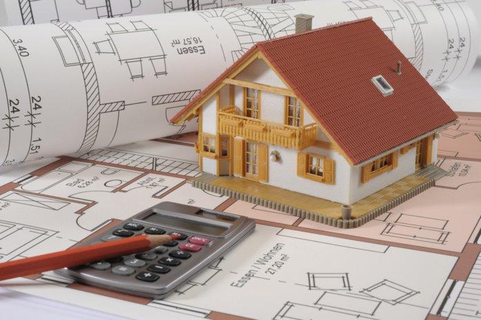 Игрушечный домик и калькулятор на инженерных планах
