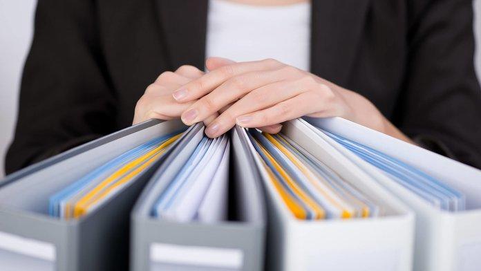 Женщина подготовила папки с документами