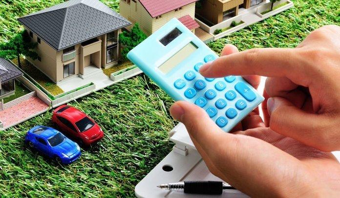Человек считает на калькуляторе возле символичной схемы имущества