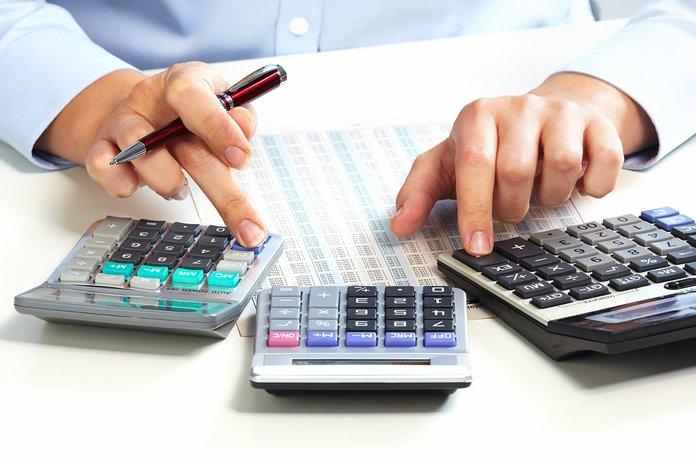 Человек считает налоги на калькуляторе