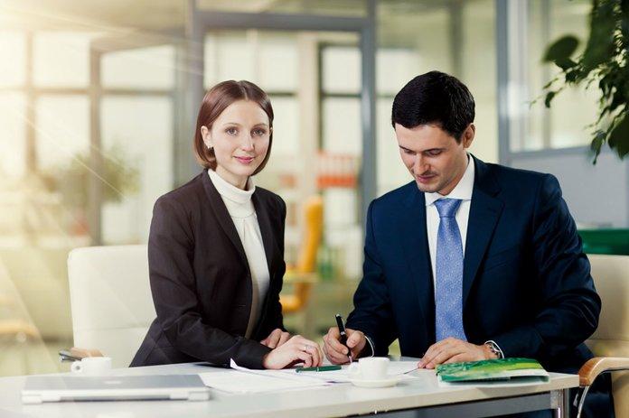 Мужчина и женщина оформляют заявление в банке