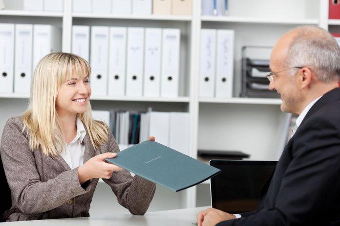 Сотрудница передает клиенту договор