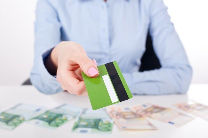 Сотрудница банка выдает кредитную карточку
