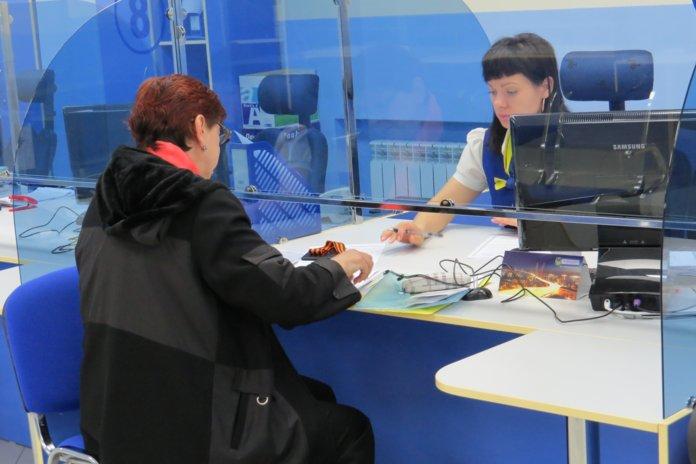 Женщина оформлят документы в офисе